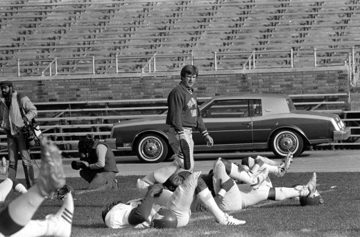 Philadelphia Eagles head coach Dick Vermeil observes his team limbering up during a workout at JFK Stadium in Philadelphia, Nov. 19, 1982, in preparation for Sunday's NFL game against the Cincinnati Bengals. It is the first game for both teams since the season was interrupted by the players' strike. (AP Photo/Bill Ingraham)