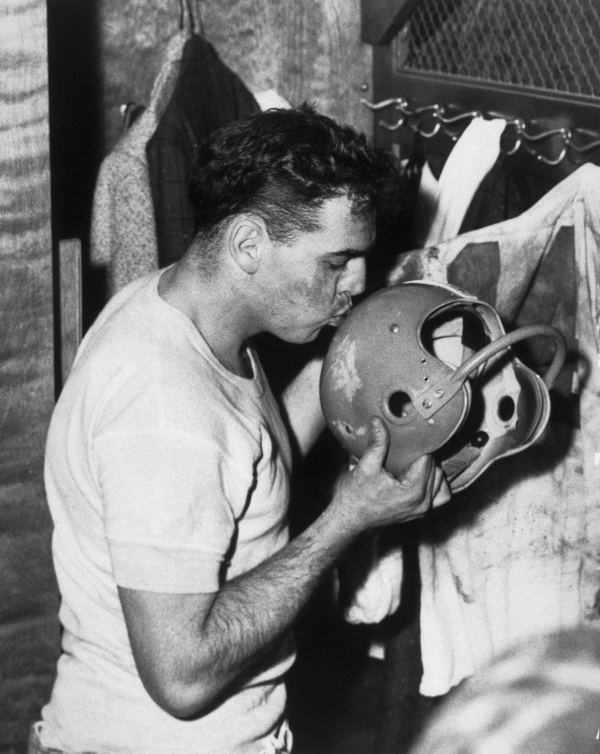 Original caption: Otto Graham, Cleveland quarterback, kisses his helmet after the Detroit Lions game in which the Browns beat the Lions, 56-10 (Dec. 26). Graham announced that he plans to retire from football. (Copyright Bettmann/Corbis / AP Images)
