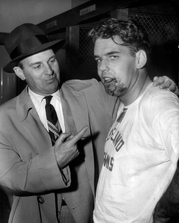 Coach Paul Brown shows off the 15 stitches a doctor put on quarterback Otto Graham's face during half time during the game his Cleveland Browns won from the San Francisco 49ers in Cleveland, Ohio, on Nov. 15, 1953. Graham, unable to find a receiver, ran with the ball during the second quarter and was hurt when he was knocked out of bounds after running to a first down. (AP Photo/Julian C. Wilson)