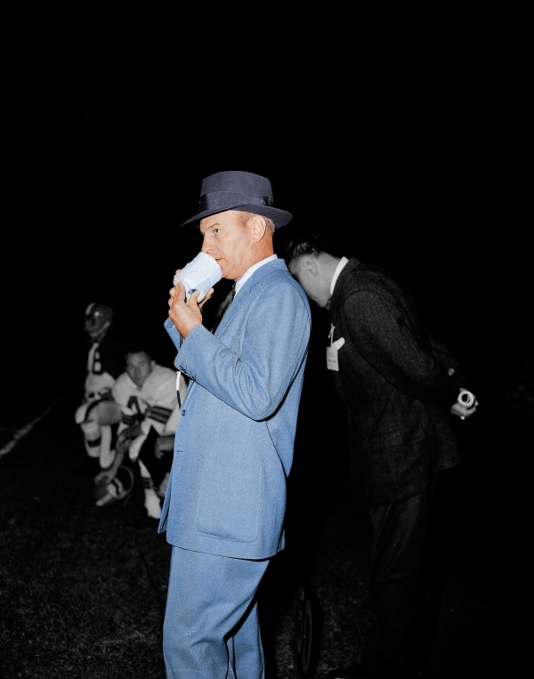 Cleveland Browns Coach Paul Brown talks into microphone of transmitter to communicate with player with receiver in helmet during exhibition game in Chicago, Sept. 21, 1956. (AP Photo)