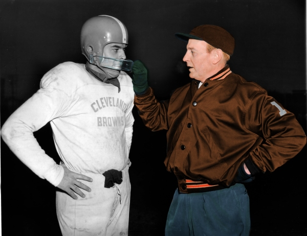 Cleveland Browns coach Paul Brown, right, who played quarterback in his younger days, checks the protective mask of his quarterback Otto Graham, who wears a mask to guard a face injury sustained earlier in the season. Graham's quarterbacking and passing have kept the Browns in the top of professional football this year and in past seasons. This photo was taken at an unknown location, on Dec. 8, 1953. (AP Photo)